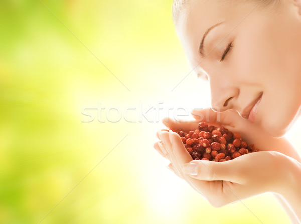 Beautiful young woman with handful of fresh strawberries Stock photo © Nejron