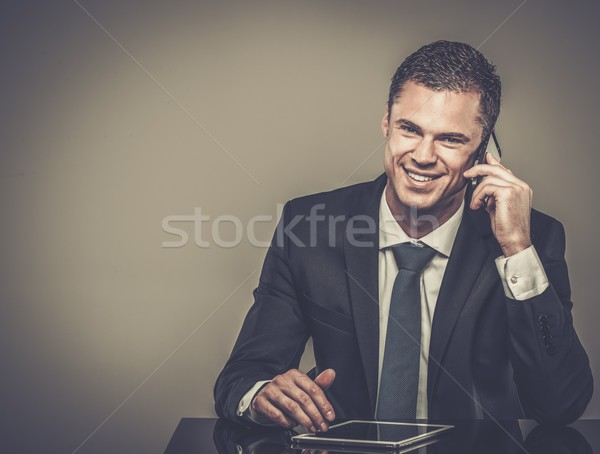 Well-dressed man in black suit with mobile phone and tablet pc Stock photo © Nejron