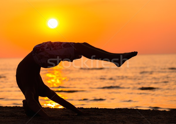 Silhouettes a young man doing jumps on a beach against sunset  Stock photo © Nejron