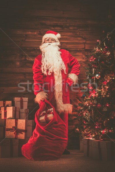 Santa Claus in wooden home interior with sack full of Christmas presents Stock photo © Nejron