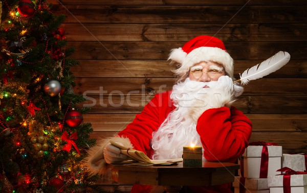 Santa Claus  in wooden home interior with letters and quill pen in hands Stock photo © Nejron