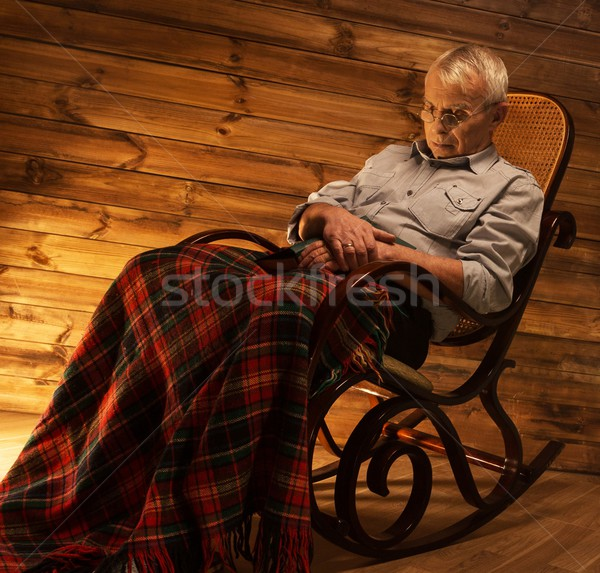 Senior man fell asleep on rocking chair in homely wooden interior  Stock photo © Nejron