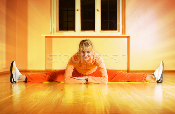 Beautiful fitness trainer does splits on a floor surrounded by t Stock photo © Nejron