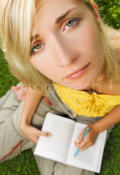 Sad young girl sitting outdoors on a grass and reading book Stock photo © Nejron
