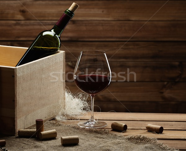 Bottle and glass of red wine on a wooden table  Stock photo © Nejron