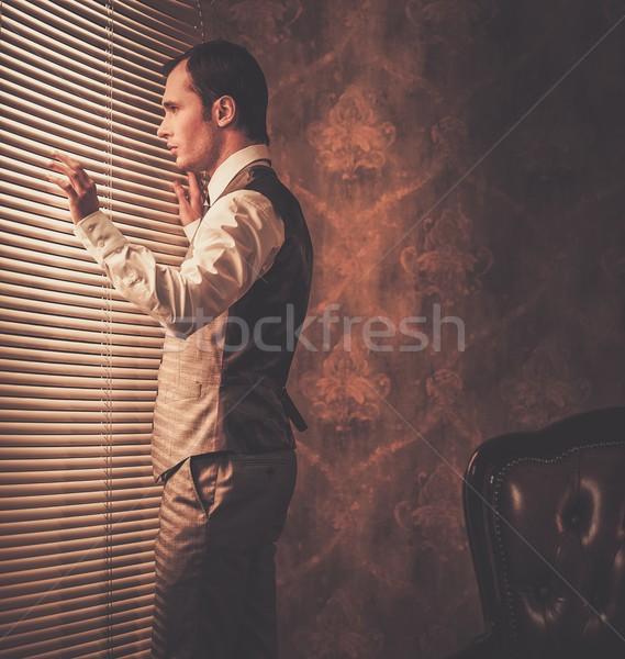 Well-dressed man looking through jalousie  Stock photo © Nejron