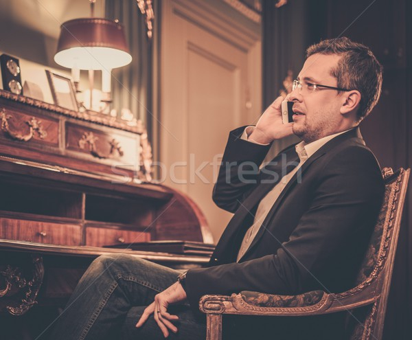 Confident middle-aged man with mobile phone in luxury interior  Stock photo © Nejron