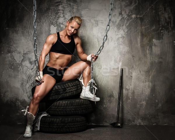 Beautiful muscular bodybuilder woman sitting on tyres and holding chains  Stock photo © Nejron