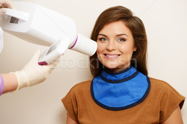 Dentist making x-ray picture of a happy female patient  Stock photo © Nejron
