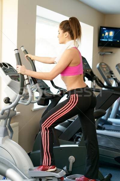 Young woman doing exercise in fitness club on training machine Stock photo © Nejron