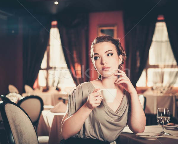Beautiful young woman with cup of coffee alone in a restaurant Stock photo © Nejron