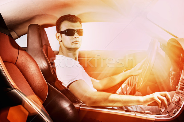 Handsome young man driving modern sport car Stock photo © Nejron