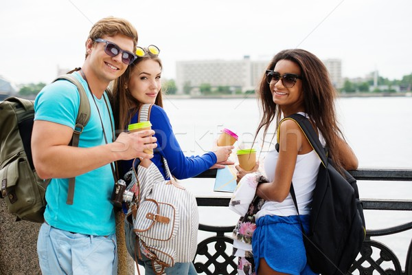 Multi-ethnic friends tourists with map and coffee cups near river in a city Stock photo © Nejron