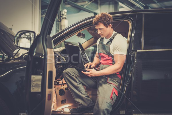 Stock photo: Serviceman making car diagnostics with laptop in a workshop