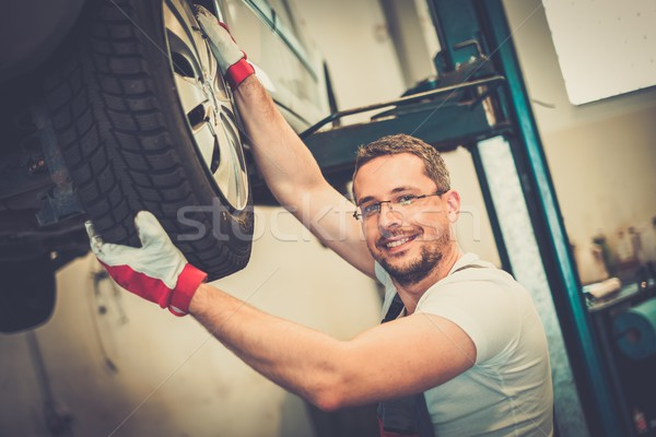 Mechanic checking wheel bearings in a car workshop  Stock photo © Nejron