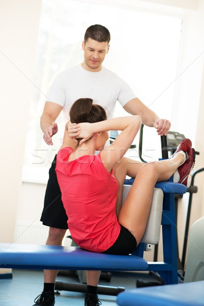 Personal fitness trainer explains to a young woman how to do abdominal exercise Stock photo © Nejron