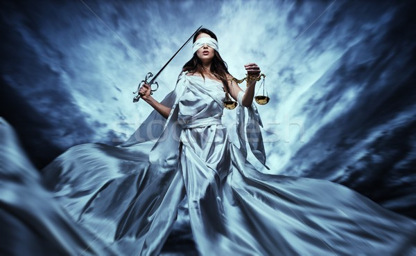 Stock photo: Femida, Goddess of Justice, with scales and sword wearing blindfold against dramatic stormy sky