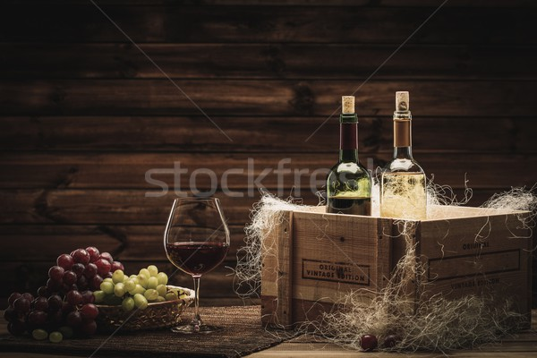 Bottles of red and white wine, glass and grape on a wooden interior  Stock photo © Nejron
