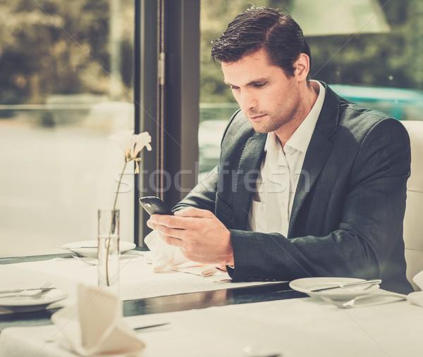 Przystojny mężczyzna telefonu komórkowego restauracji działalności żywności człowiek Zdjęcia stock © Nejron