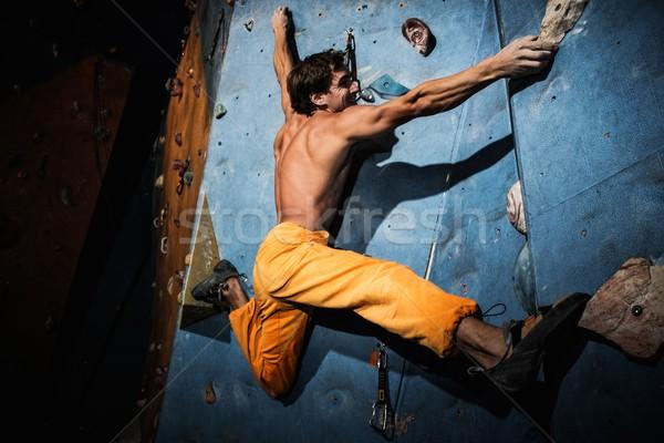 Muscular man practicing rock-climbing on a rock wall indoors  Stock photo © Nejron