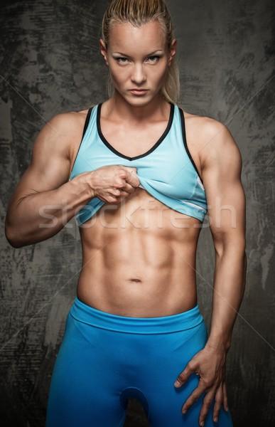 Aantrekkelijk bodybuilder meisje tonen abdominaal spieren Stockfoto © Nejron