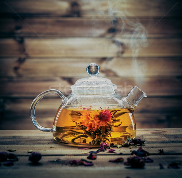 Glass teapot with blooming tea flower inside against wooden background  Stock photo © Nejron
