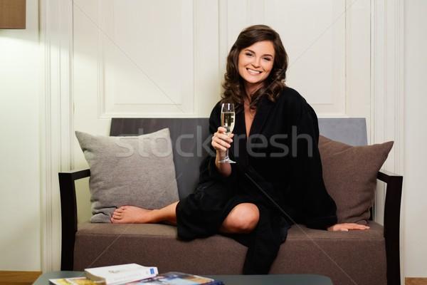 Mulher roupão de banho relaxante vidro champanhe quarto de hotel Foto stock © Nejron