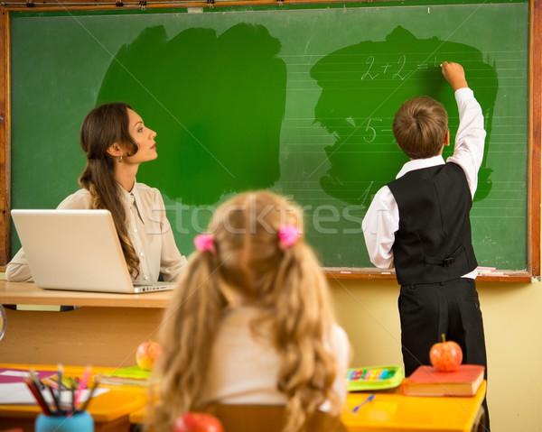 Little schoolboy answering near blackboard in school Stock photo © Nejron