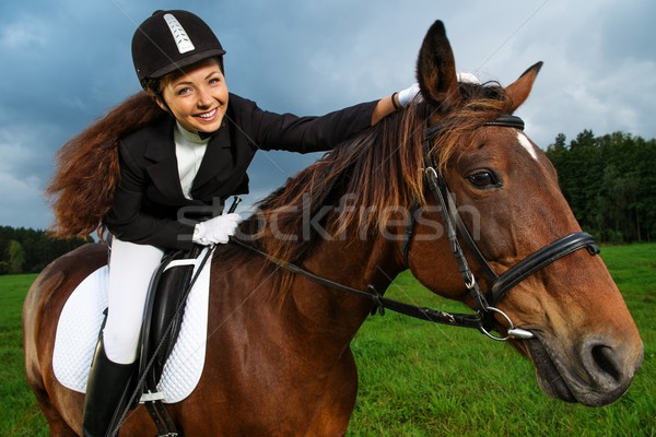 Stock photo: Beautiful smiling girl sitting on a horse outdoors