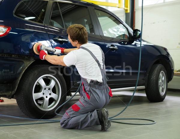 Serviceman polishing car body with machine  in a workshop Stock photo © Nejron