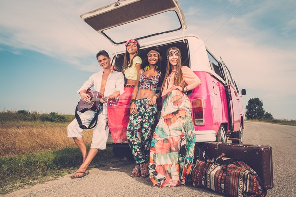 Stock photo: Multi-ethnic hippie friends with guitar on a road trip