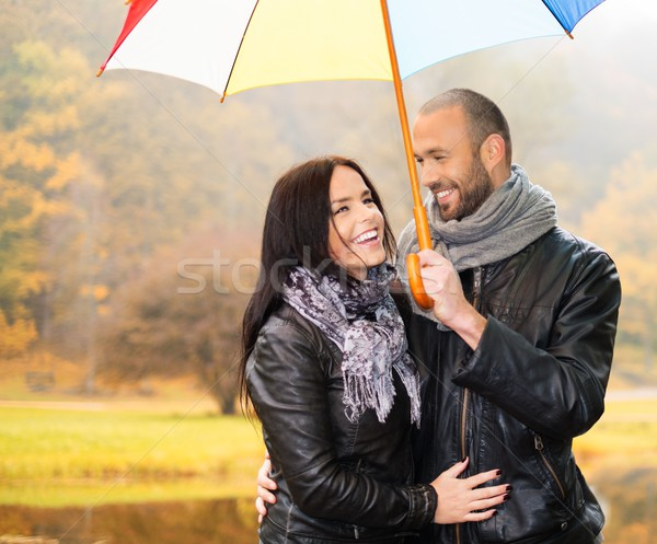 Happy middle-aged couple with umbrella outdoors on beautiful rainy autumn day   Stock photo © Nejron