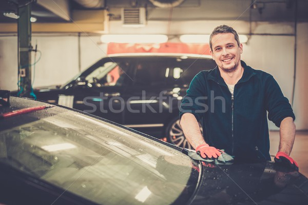 Cheerful worker wiping car on a car wash Stock photo © Nejron