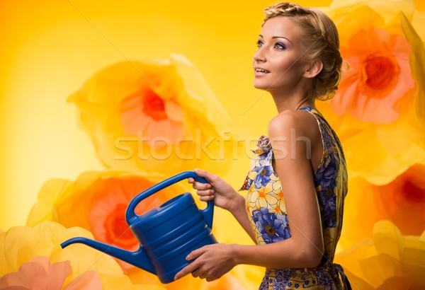 Beautiful dreaming woman in colourful dress with watering can among big yellow flowers Stock photo © Nejron