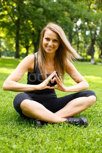 Young happy sporty girl showing heart sign with her hands on a meadow in a park Stock photo © Nejron