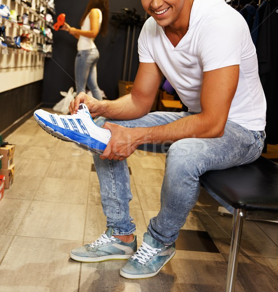Young handsome man choosing sport footwear in sport outlet Stock photo © Nejron