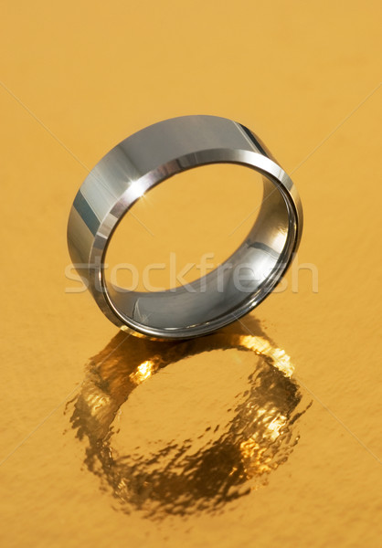 Silver ring reflected in golden surface Stock photo © Nejron
