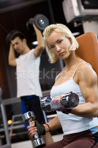 Strong beautiful woman lifting heavy dumbbells Stock photo © Nejron