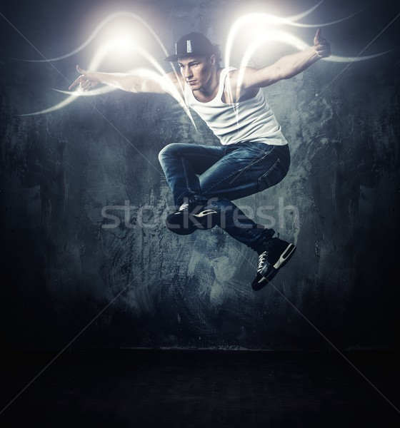 Stylish man dancer showing break-dancing moves with magic beams around him  Stock photo © Nejron