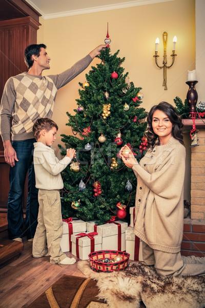 Stock photo: Happy family decorating Christmas tree