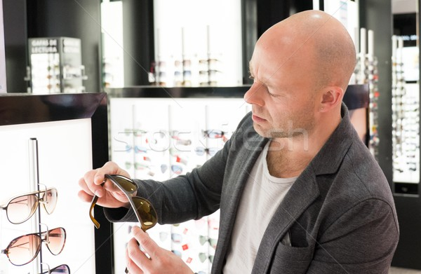 Middle-aged man choosing sunglasses in a shop Stock photo © Nejron