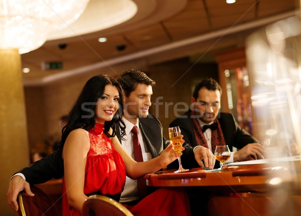 Young people in evening dress behind poker table in a casino Stock photo © Nejron