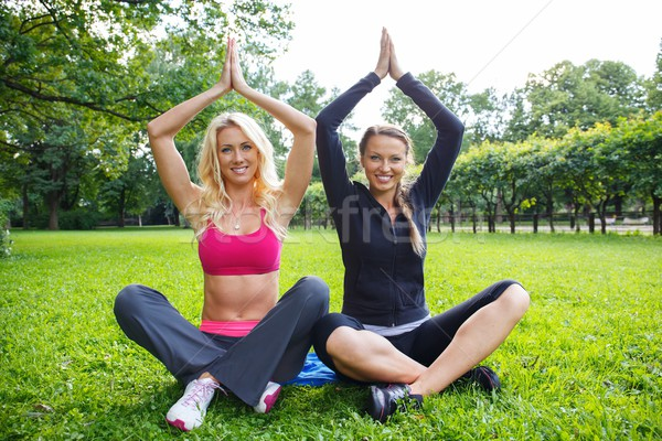 Two smiling athletic girls sitting in yoga pose on a grass in a park Stock photo © Nejron