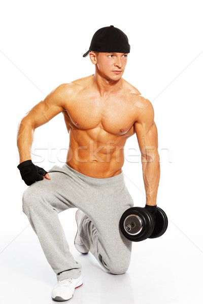 Handsome young muscular man exercising with dumbbells Stock photo © Nejron