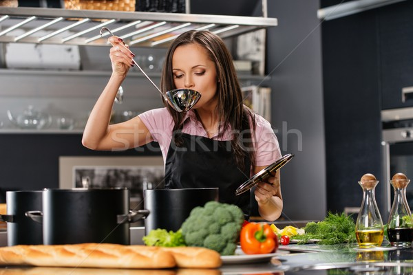 Cheerful young woman in apron on modern kitchen with ladle tasting from pot Stock photo © Nejron