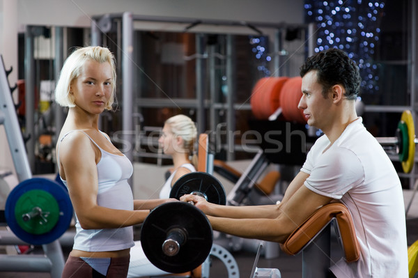 Handsome young man lifting weights assisted by a female trainer Stock photo © Nejron
