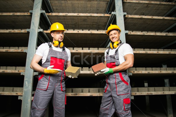 Two workers in a storage room on a factory holding their product Stock photo © Nejron