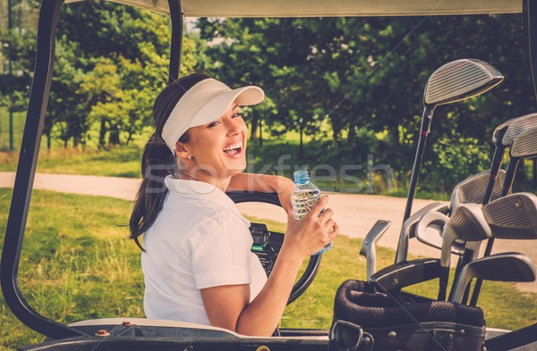 Young cheerful woman with bottle of water driving golf cart  Stock photo © Nejron