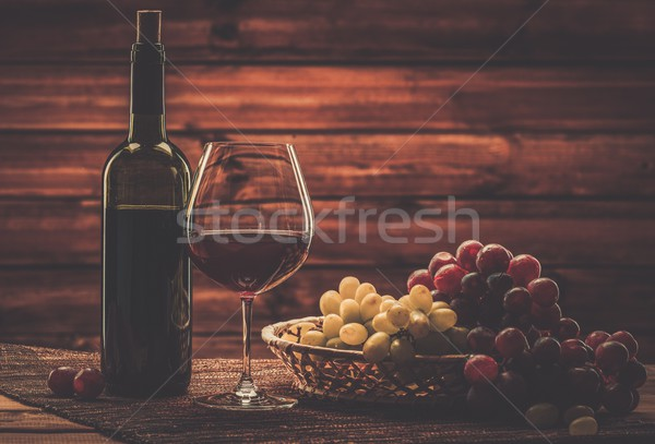 Stock photo: Bottle of red wine, glass and grape in basket in wooden interior