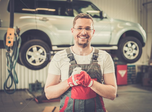 Cheerful serviceman wearing overall in car workshop  Stock photo © Nejron